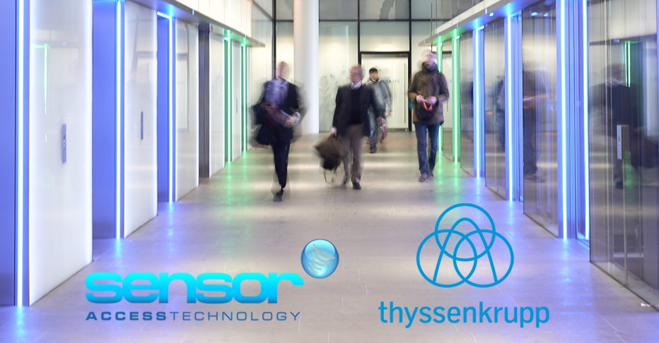 Image of men walking down a corridor adjacent to lifts, with the Sensor and Thyssen logos seen at the bottom of the image