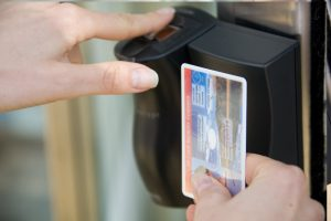 Image of a woman scanning her smart card and using biometrics - finger print recognition
